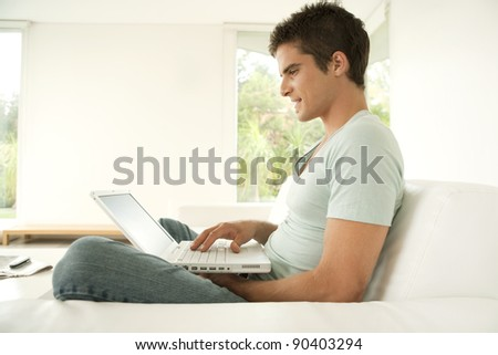 Young man using a laptop computer while sitting down on a sofa at home.