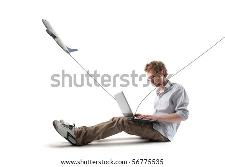 Young man using a laptop with plane flying away from it