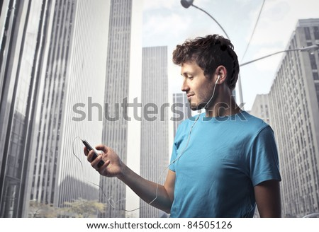 Young man using a mobile phone with cityscape in the background