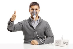 Young man using a nebulizer and showing thumbs up isolated on white background