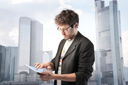 Young man using a tablet pc with cityscape in the background
