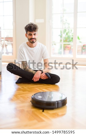 Young man using automatic vacuum cleaner to clean the floor, controling machine housework robot #1499785595