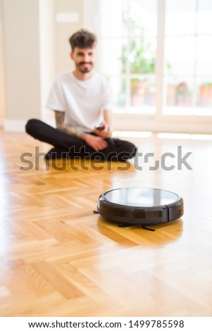 Young man using automatic vacuum cleaner to clean the floor, controling machine housework robot #1499785598