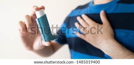 Young man using blue asthma inhaler for relief asthma attack. Pharmaceutical product is used to prevent and treat wheezing and shortness of breath caused asthma or COPD. Health care concept. Close up.