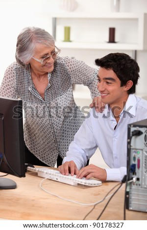 Young man using computer and happy senior woman