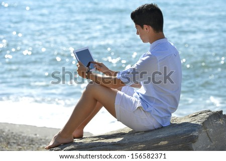 Young man using Digital Tablet on the beach