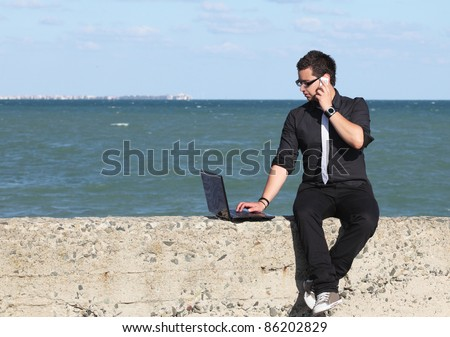 Young man using laptop and phone at beach