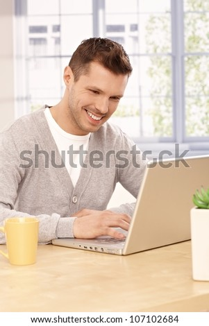 Young man using laptop computer at home, smiling.