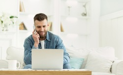 Young man using laptop having phone conversation, working at home, panorama with free space