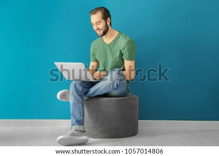 Young man using laptop indoors #1057014806