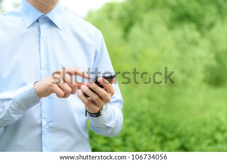 Young man using mobile smart phone in the park.