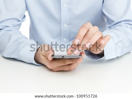 Young man using smart phone by the desk