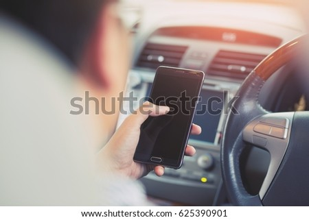 Young man using  smart phone mobile phone in car.
