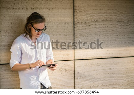 Young man using tablet outdoors #697856494