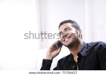 Young man using telephone, smiling and calling on white background