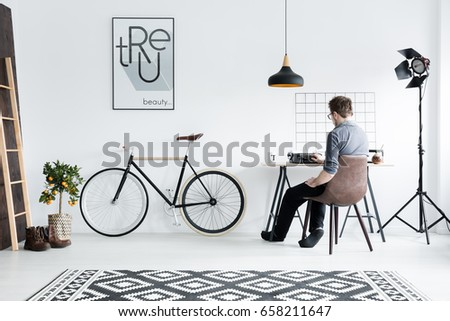 Young man using typewriter in his minimalistic room #658211647