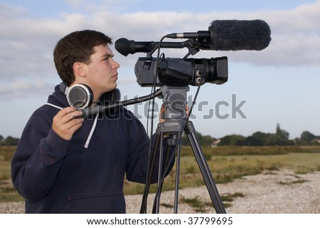 Young man videoing outside