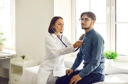 Young man visiting doctor for health exam. Serious middle aged female physician with stethoscope sitting on modern examination couch and listening to male patient's lungs or checking his heartbeat
