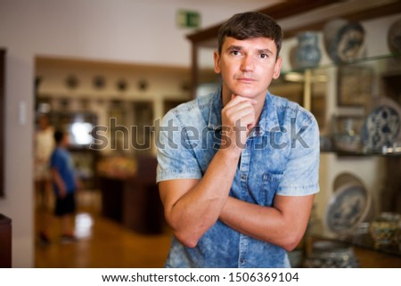 Young man visiting exposition of historical museum with exhibits of antiquity