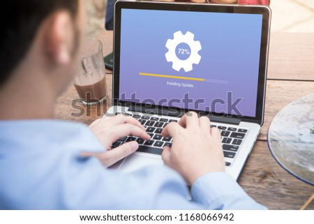 Young man waiting for installing update process with gearbox percentage progress and loading bar on laptop / computer at the outdoor cafe #1168066942