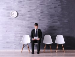 Young man waiting for job interview in reception hall