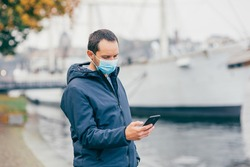 Young man waiting for the ferry in a protective mask during pandemics. Safe travel concept.