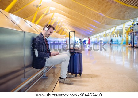 Young man waiting listening music and using mobile phone at the airport with a suitcase