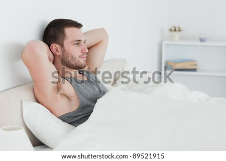 Young man waking up in his bedroom