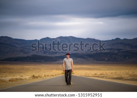 Young man walking alone through an empty street in the desert of Death Valley National Park. Loneliness, sadness , depression and solitude concept in nature.