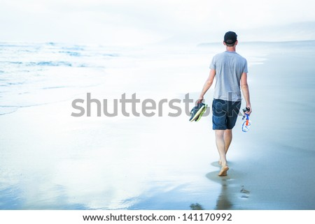 young man walking at sea shore alone and relaxed