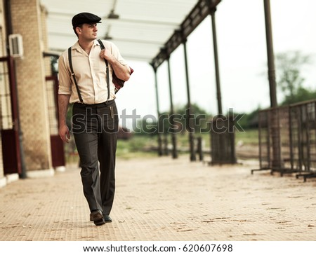 Young man walking at the  old vintage train station.Retro emigration concept.