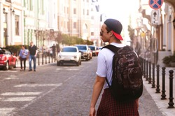 young man walking down the city street on a sunny day