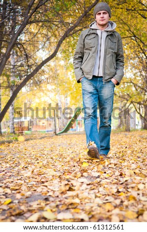 Young man walking in the autumn park