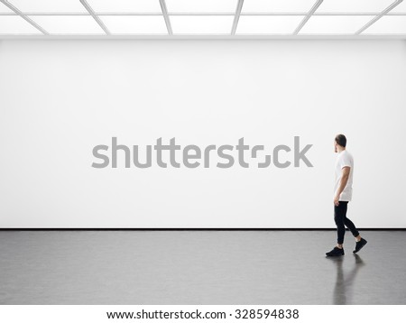 Young man walking in the empty gallery - Shutterstock ID 328594838