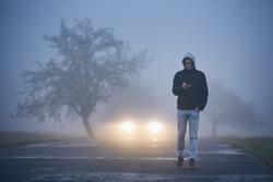 Young man walking on road and using phone. Car approaching in thick fog.