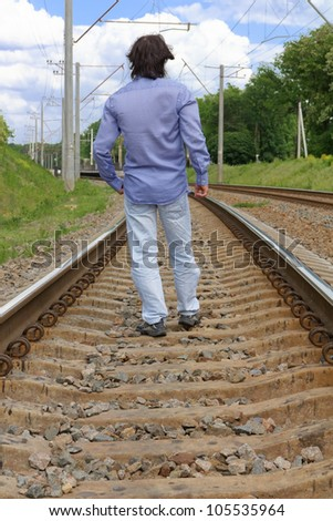 Young man walking on the railway tracks