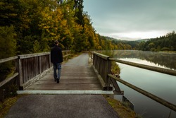 Young man walking on wooden bridge with Vltava river and autumn trees
