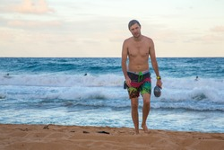 Young man walking out of the water on the beach on the Kauai island, Hawaii