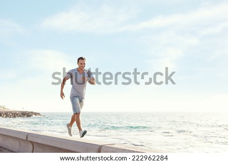 young man walking over the pier near the ocean with earphones and music