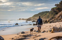 Young man walking the dog on the beach at the Strait Natural Park, Tarifa, Cadiz Province, Andalusia, Spain