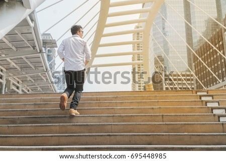 Young man walking up stair in modern city feeling relax and enjoy. Back side of Businessman wear glasses,boots with white shirt ,jeans after work. Light Tone Effect with copy space lifestyle concept. #695448985