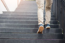 Young man walking up the stairs with sun sport background. step for success.