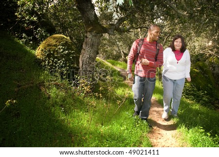Young man walking with his visually impaired friend on a forest path using sighted guide technique