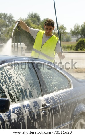 Young man washing a car using compression water