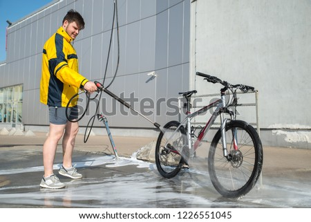 young man washing bicycle at carwash. lifestyle