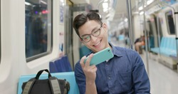 young man watch the video with phone on the MRT or train