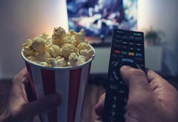 young man Watching a Movie in his living room with popcorn and remote control, Point of view shot