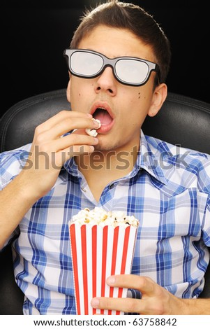 Young man watching movie in 3D glasses at cinema