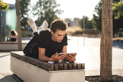 Young man watching movie on digital tablet while lying on bench at college campus. High quality photo