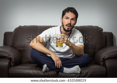 Young man watching sports match on tv at home. Very focused on it, holding a beer mug. Photo stock ©
